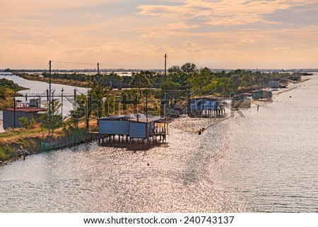 landscape of the wetland in Comacchio, Ferrara, Italy - fishing huts with net on the canal of the lagoon  - stock photo