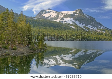 Landscape of Tioga Lake with reflections of the Sierra Nevada Mountains in calm water, Yosemite National Park, California, USA - stock photo