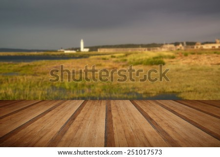 Landscape of wetlands during stormy sky sunset towards lighthouse with wooden planks floor - stock photo