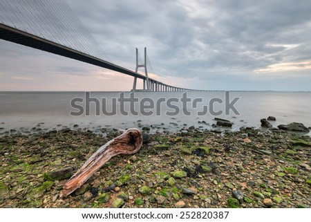 Landscape on the banks of the Tagus River in Lisbon with panoramic views of the Vasco da Gama Bridge, with beautiful colors of Sunrise. Photo fine art with wooden trunk and long exposure effect. - stock photo