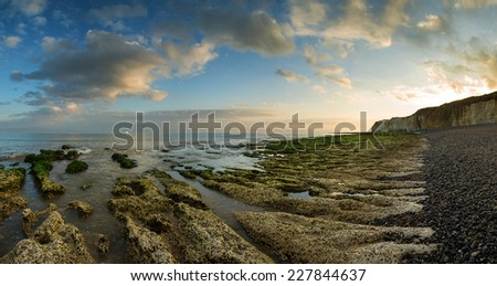 Landscape panorama beautiful sunset over rocky coastline - stock photo
