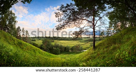 landscape panorama of the river valley with a lonely pine on the high bank in the foreground and fields and meadows and forests and white clouds in the background on a clear evening before sunset - stock photo