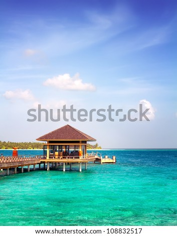 Landscape photo of Island in ocean, over water villa with endless swimming pools. Maldives. - stock photo