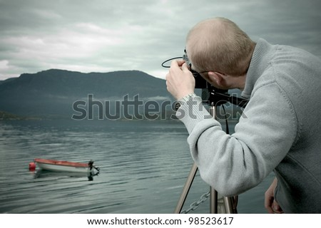 landscape photographer at a fjord in norway - stock photo