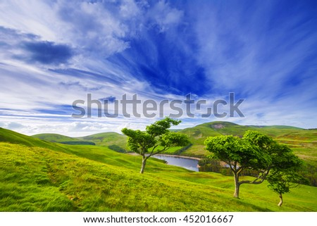 Landscape scenery of green valley with trees, river and cloudy blue sky. Pentland hills, Scotland - stock photo