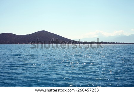 Landscape sea and island, glare from the sun on the water - stock photo