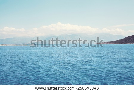 Landscape sea and mountains with clouds in the distance, soft pastel colors photo - stock photo