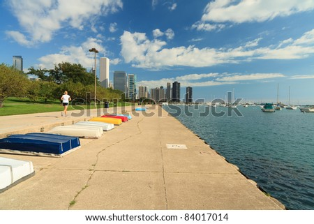 Landscape skyline view of the Lakefront trail in Grant Park along Lake Michigan in Chicago with a polarized blue sky and a jogger exercising. - stock photo