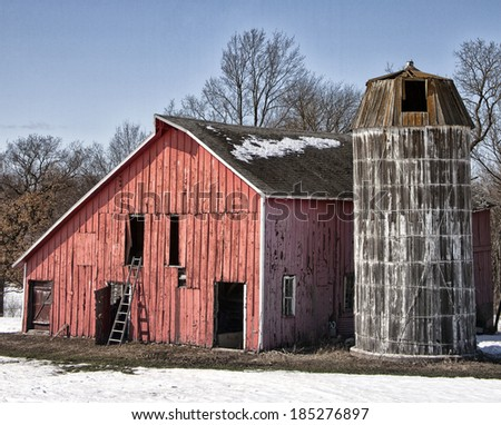 Landscape springtime image of an old farmstead, with weathered barn with wooden silo.  Springtime in Wisconsin - stock photo
