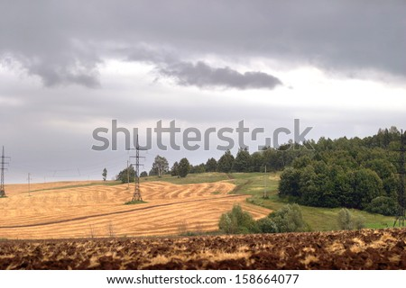 landscape storm clouds and rain over the field in the late summer - stock photo