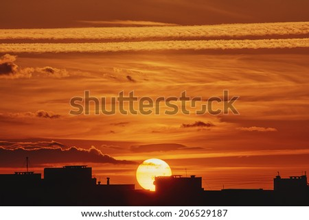 Landscape - sun at sunset with clouds and path of the aircraft, foreground of silhouettes of rooftops - stock photo