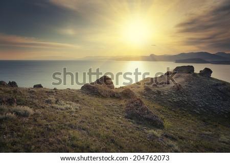 Landscape. Sun over the seacoast at sunset - stock photo
