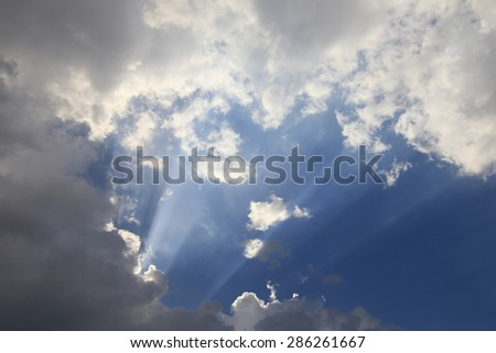 landscape sun rays through the clouds in the blue sky - stock photo