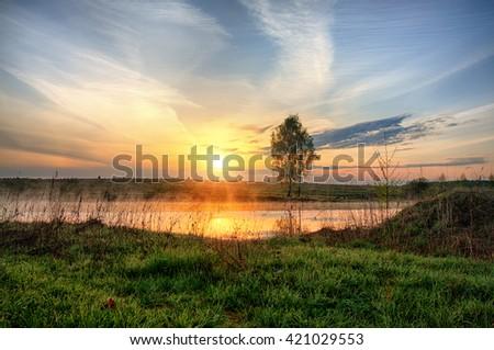 Landscape: sunrise over lake with tree and fog - stock photo