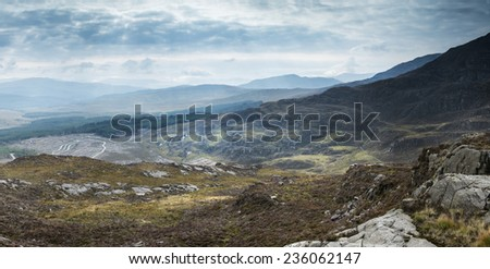 Landscape view from top of mountain on misty morning across countryside - stock photo