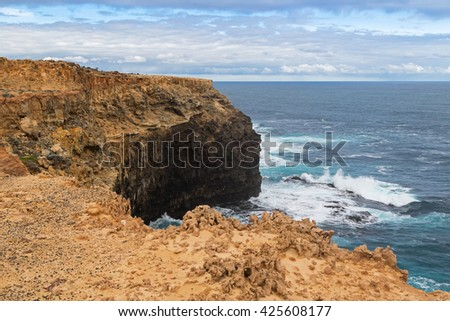 Landscape view of coastal cliff at Petrified Forest Walk with deep blue sea water splashing at Cape Bridgewater in Victoria, Australia - stock photo