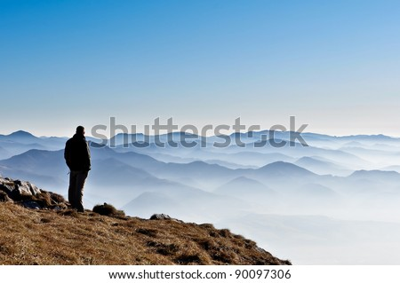 Landscape view of misty autumn mountain hills and man silhouette - stock photo
