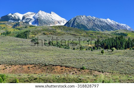 landscape view of the alpine scenery with snow covered mountains during foliage season at Kebler and Ohio Passes - stock photo