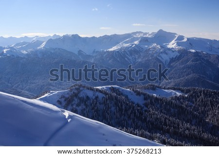 landscape view of the valley with old trail on slope covered with snow and mountain ridge covered with forest - stock photo