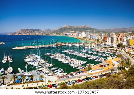 Landscape with a bay full of yachts and leisure people on the beach (Spain's Costa Brava) - stock photo