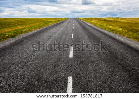 Landscape with a black asphalt road - stock photo