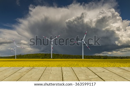 Landscape with a field of rape and wind electric-turbines.  Conceptual image illustrating production of alternative sources of energy - stock photo
