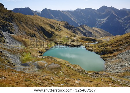 Landscape with a glacial lake between rocky mountains - stock photo