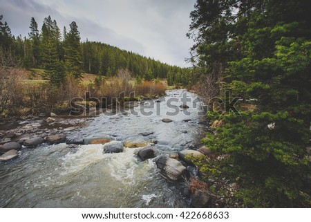 Landscape with a mountain river going through the wilderness. - stock photo