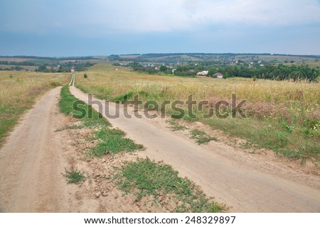 Landscape with a road in the field and rising storm on the horizon - stock photo