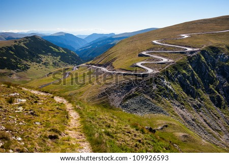 Landscape with a winding road and a trail on mountains - stock photo