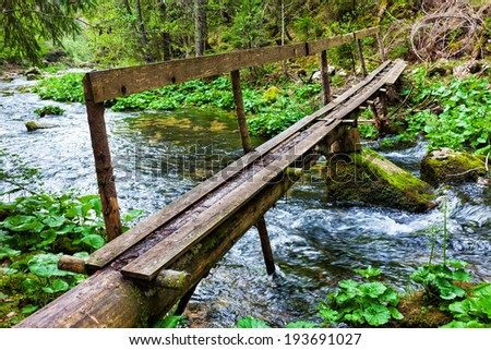 Landscape with a wooden bridge over a river and lush forest - stock photo