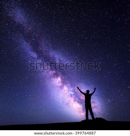 Landscape with colorful purple Milky Way. Night sky with stars and silhouette of a happy man with raised up arms on the mountain. Beautiful Universe. Space background - stock photo