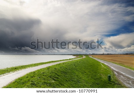 landscape with dramatic sky in the netherlands - stock photo