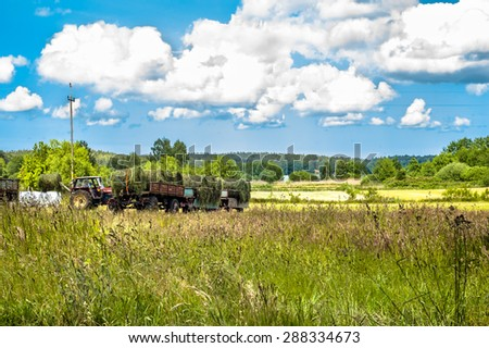 Landscape with haymaking. The tractor and the trailer of hay in a field. Fields and meadows at summer, the idyllic rural landscape and agricultural. Blue sky with clouds and sunny day. - stock photo