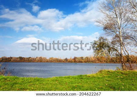 Landscape with lake and green grass. There is remote fisherman in boat on the water - stock photo