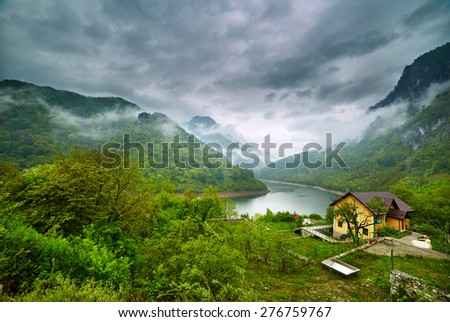 Landscape with lake and misty forest in mountains in a rainy day - stock photo
