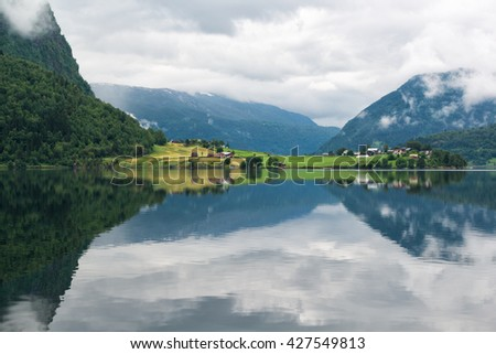 Landscape with lake and rural land with colored houses, mirror reflection of the mountains in the water, Norway - stock photo