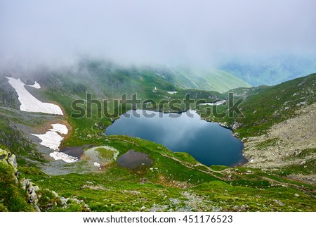 Landscape with lake Capra in Romanian Carpathian mountains - stock photo