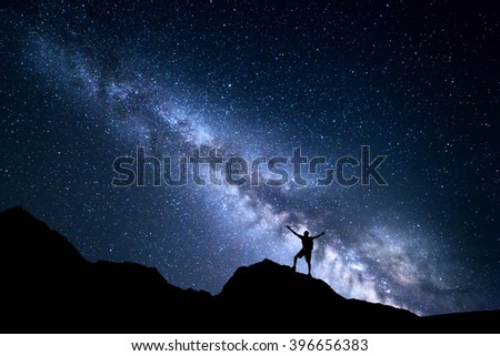 Landscape with Milky Way. Night sky with stars and silhouette of a happy man with backpack and raised up arms on the mountain. Space background - stock photo