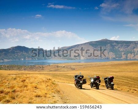 Landscape with mountain lake and three motorbikes - stock photo