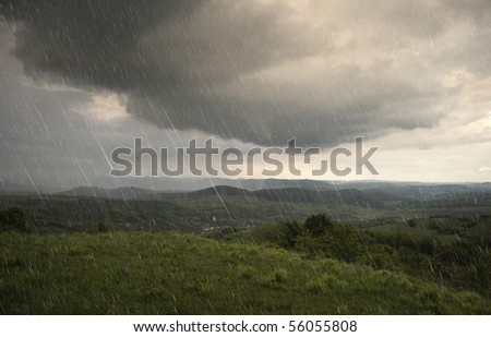 landscape with rain and dramatic clouds over hills - stock photo