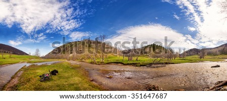 Landscape with river, hills, sky and touring bike  - stock photo