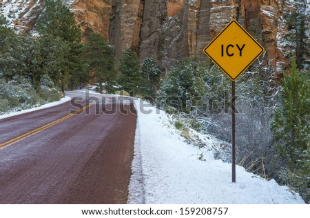 Landscape with road in winter forest and road sign ICY - stock photo