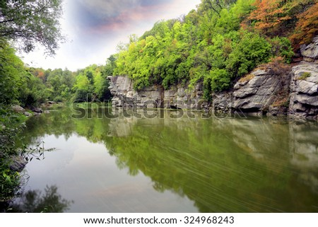 Landscape with rocks over river in deep green forest - stock photo