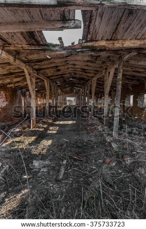 Landscape with ruins of old industrial buildings for farm animals. Interior of an abandoned pigsty plunder and waste. The collapse of economy. Selective focus. As background for design of crisis - stock photo