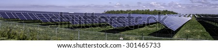 Landscape with solar energy farm nearby Strathroy, Ontario, Canada. In the field are placed thousands of solar panels on frames generating green energy.   Photo taken May 2015. - stock photo