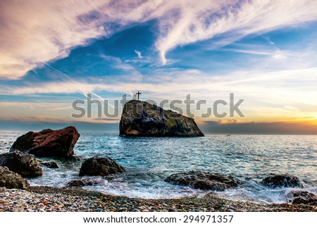 Landscape with sunset on the blue sea beach, rocks and dramatic sky.  - stock photo