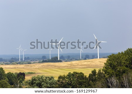landscape with wind turbines forest and fields. - stock photo
