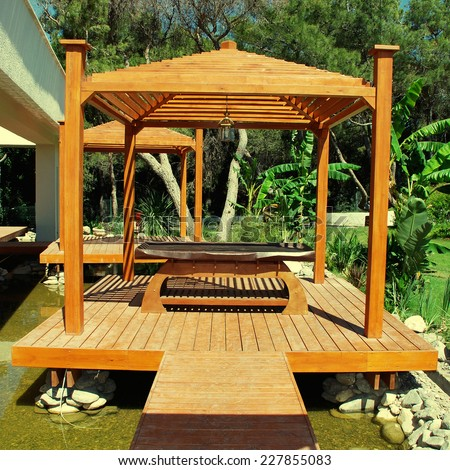 Landscape with wood pavilion for massage in tropical garden on summer resort, instagram effect, square toned image - stock photo