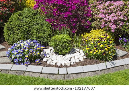Landscaped flower garden with lots of colorful blooms - stock photo